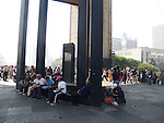 PEOPLE SIT ON BENCH UNDER MEXICO CITY'S MONUMENT TO THE REVOLUTION