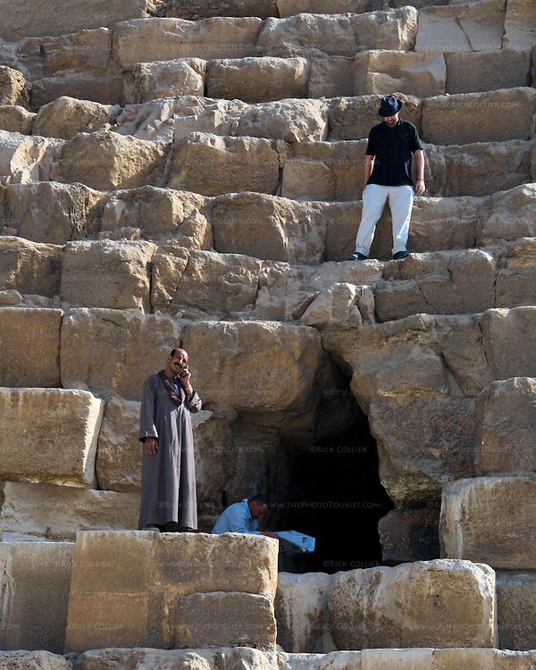 Giza, Cairo, Egypt -- A tourist looks down from above on local staff attending their daily routines on the Great Pyramid of Khufu (Cheops) at Giza. © Rick Collier / RickCollier.com.