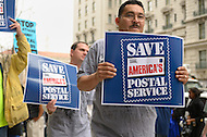 November 21, 2011  (Washington, DC)  Jorge Lopez (right), of the Sheet Metal Workers Local 100, holds a sign as he protests in front of the National Press Building in Washington to rally against cuts within the Postal Service.  U.S. Postmaster General Patrick R. Donahoe was inside speaking to members of the National Press Club.   (Photo by Don Baxter/Media Images International)