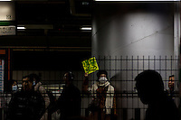 "A Japanese woamn holds a sign saying ""Let's go to vote"" on the platform of Ogikubo Station as politicians campaign nearby. Ogikubo, Tokyo, Japan. Friday December 14th 2012"