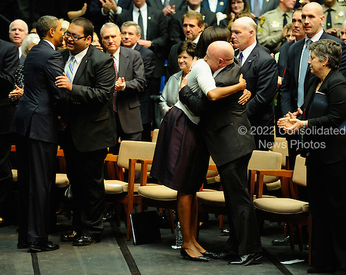 "(L-R) United States President Barack Obama hugs Daniel Hernandez, Jr., an intern of U.S. Representative Gabrielle Giffords (Democrat of Arizona), as first lady Michelle Obama hugs NASA astronaut Mark Kelly, husband of Giffords at the event ""Together We Thrive: Tucson and America"" honoring the January 8 shooting victims at McKale Memorial Center on the University of Arizona campus on Wednesday, January 12, 2011 in Tucson, Arizona. The memorial service is in honor of victims of the mass shooting at a Safeway grocery store that killed six and injured at least 13 others, including U.S. Representative Gabrielle Giffords (Democrat of Arizona), who remains in critical condition after being shot in the head. Among those killed were U.S. District Judge John Roll, 63; Giffords' director of community outreach, Gabe Zimmerman, 30; and 9-year-old Christina Taylor Green. .Credit: Kevork Djansezian / Pool via CNP"