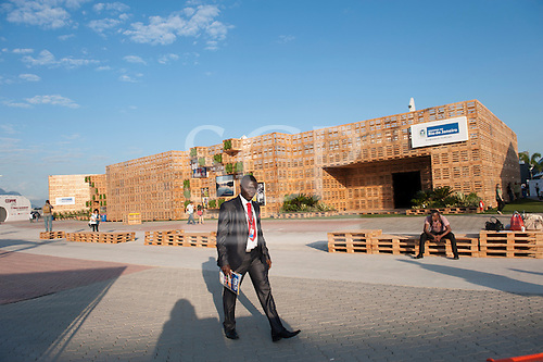 A member of the delegation of Ghana walks past the Rio de Janeiro Pavilion at the United Nations Conference on Sustainable Development. The pavilion is constructed from wooden palettes in the Athletes Park, adjacent to the RioCentro UN venue. (Rio+20), Rio de Janeiro, Brazil, 14th June 2012. Photo © Sue Cunningham.
