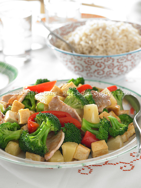 Stir fry with broccoli, tofu, red peppers, pork, and pineapple. Bowl of brown rice in background.