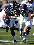 Nevada's Brandon Wimberly (4) tries to break free from Northwestern State's Bert White (10) and Brashard Booker (21) during the first half of an NCAA college football game Saturday, Sept. 15, 2012, in Reno, Nev. (AP Photo/Cathleen Allison)
