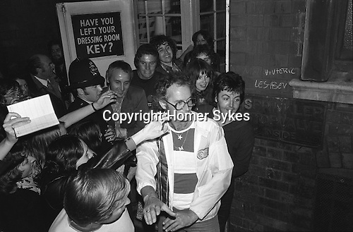"Paul and Linda McCartney Wings Tour 1975.   Paul leaves by the stage door, after the Liverpool performance. Fans clamour to catch a glimpse of him. Bel Bush the promoter holds back fans. England. Brian Brolly managing Director of MPL under the word ""key"" The photographs from this set were taken in 1975. I was on tour with them for a children's ""Fact Book"". This book was called, The Facts about a Pop Group Featuring Wings. Introduced by Paul McCartney, published by G.Whizzard. They had recently recorded albums, Wildlife, Red Rose Speedway, Band on the Run and Venus and Mars. I believe it was the English leg of Wings Over the World tour. But as I recall they were promoting,  Band on the Run and Venus and Mars in particular."