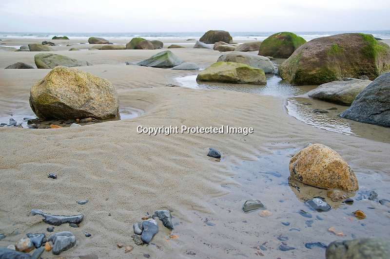 Rocks and Boulders on a Misty Beach during Incoming Tide on the Coast of Maine