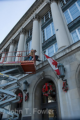 Workers installing Christmas decorations on office building
