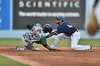 Asheville Tourists second baseman Carlos Herrera (4) fields the ball and attempts to tag John Polonius (1) as he slides in safely during a game against the Augusta GreenJackets at McCormick Field on August 6, 2016 in Asheville, North Carolina. The GreenJackets defeated the Tourists 11-4. (Tony Farlow/Four Seam Images)