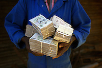 A man fortunate to have work holds his monthly wages, millions of Zimbabwean dollars that equate to just over £80. His pay includes a travel allowance which, due to inflation, is now greater than the salary itself. The cost of living doubled in the month of April 2007 as Zimbabwe's inflation reached 3,700% per annum.
