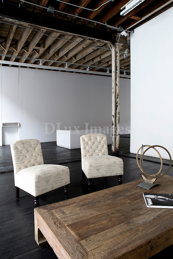 Armchairs and wooden coffee table in industrial space with exposed beams and wooden flooring