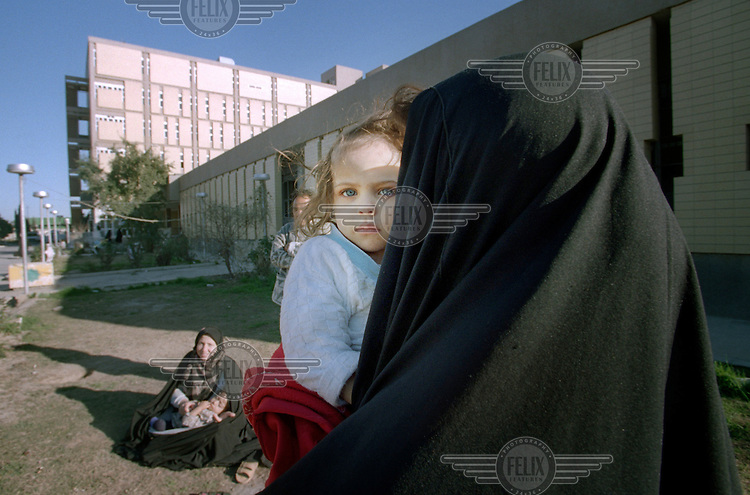"""(February 1998)    A girl and her mother outside t the Saddam hospital in Baghdad.    <br /> Due to UN sanctions the hospital was lacking many medicines, and the civilians suffered due to lack of food as well. <br />  Former U.N. Humanitarian Coordinator in Iraq Denis Halliday estimated the resulting deaths : """"Two hundred thirty-nine thousand children 5 years old and under"""" as of 1998.<br /> <br /> The sanctions against Iraq were a near-total financial and trade embargo imposed by the United Nations Security Council on the Iraqi Republic.<br /> <br /> <br /> ©Fredrik Naumann/Felix Features"""