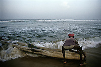 A fisherman tries to go into the sea with his Catamaran at Kovalam beach, Trivandrum, Kerala, India.