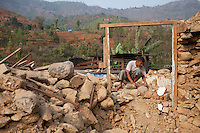 A Nepalese man clears the rubble of his destroyed house in the earthquake at 49 Kilo, near Kathmandu, Nepal. May 8, 2015