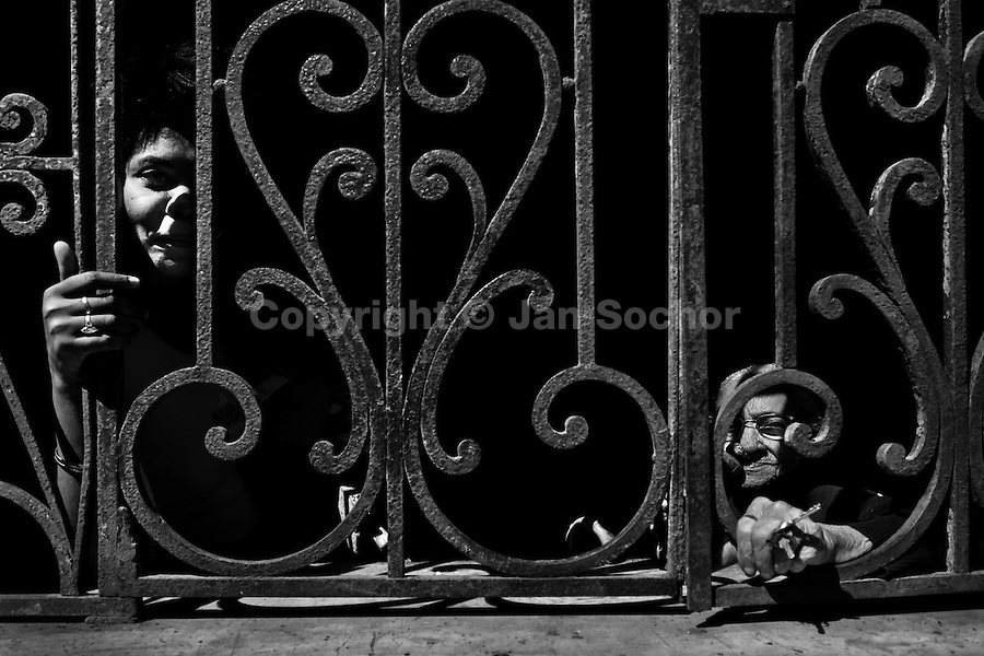 Cuban women seen in the shadow behind the window grill during a hot afternoon in Havana, Cuba, 4 February 2009.