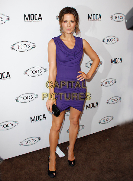 KATE BECKINSALE.The Diego Della Valle Cocktail Celebration Honoring Tod's Beverly Hills Boutique And MOCA's New Director Jerry Deitch at Tod's Boutique in Beverly Hills, California, USA..full length sleeveless purple ruched body con dress bodycon cowel neck hand on hip tanned black peep toe shoes clutch bag .CAP/RKE/DVS.©DVS/RockinExposures/Capital Pictures.