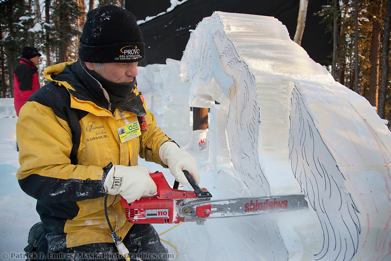 "2009 World Ice Art championships, Fairbanks, Alaska. Multi-block sculpture competition. Realistic category, titled ""White Fang"" by Japanese sculptors: Junichi Nakamura; Shinichi Sawamura; Fukumi Furukawa; Takao Waki. Shinichi works on the beginning stages of a wold in a running position."
