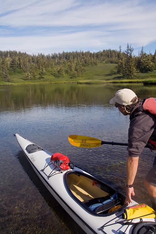 Alaska, Prince William Sound, Sea Kayaker explores a tidal lake, Unakwik Inlet, Olsen Island; David Fox, released, .