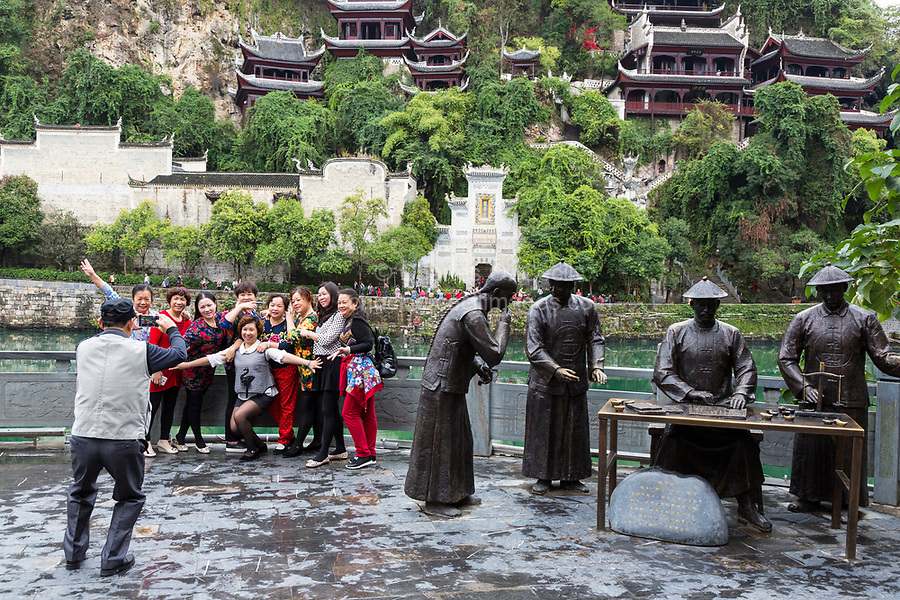 Zhenyuan, Guizhou, China.  Chinese Tourists Posing for Photo next to Sculpture Depicting Imperial Customs Agents.  Entrance to Black Dragon cave in Background.