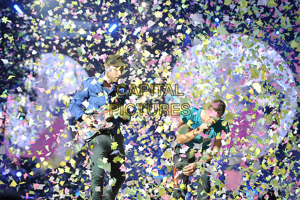 Jonny Buckland & Chris Martin of Coldplay .performing live in concert at the Emirates Stadium, London, England, UK,.1st June 2012..music gig on stage half length turquoise t-shirt microphone  paper confetti butterflies  singing microphone hat playing guitar .CAP/MAR.© Martin Harris/Capital Pictures.