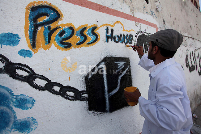 A Palestinian man draws a mural depicts a camera on a wall marking the World Press Freedom Day, in Gaza City on May 04, 2014. Photo by Ashraf Amra