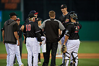 Batavia Muckdogs relief pitcher M.D. Johnson (39) talks with athletic trainer Jordan Wheat during a NY-Penn League game against the State College Spikes on July 1, 2019 at Dwyer Stadium in Batavia, New York.  Batavia defeated State College 5-4.  Also shown (L-R) pitching coach Chad Rhoades, manager Tom Lawless (10), umpire Tyler Witte, and catcher Michael Hernandez (29).  (Mike Janes/Four Seam Images)