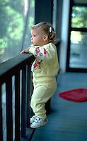 Toddler age 2 standing on porch railing looking down at the world.  Cedarville Michigan USA