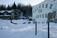 "Saturday March 10, 2007   ----   Ray Redington Jr. runs up the bank of the Yukon river as he passes the ""Welcome to Anvik"" sign at the Anvik checkpoint on Saturday morning."
