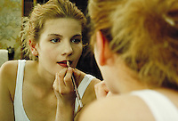 girl applying cosmetics and lip liner while looking in mirror of home bathroom. young woman. residence.