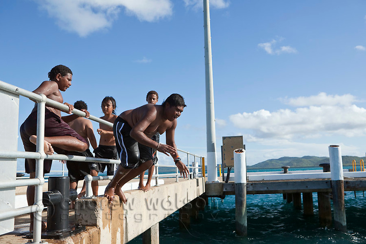 Kids leaping off the jetty at Engineers Wharf.  Thursday Island, Torres Strait Islands, Queensland, Australia