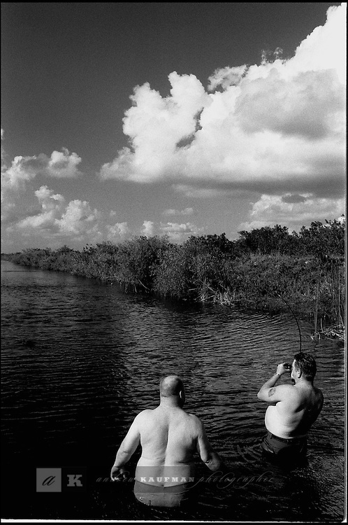 Fat Mikey and Keith fishing on a canal in the Glades.The Florida Everglades are a disappearing world. Overpopulation, the sugar and cattle industry, mismanagement of the land, droughts and bush fires are just a few of the problems the Florida Everglades are facing. Here Glen Wilsey driving his airboat. According to Glen the best thing about being a tour guide in the everglades is driving the airboats. Riding an airboat is fun but driving an airboat is an awesome feeling.