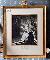 BNPS.co.uk (01202 558833)<br /> Pic: PhilYeomans/BNPS<br /> <br /> Sold for 2500 pounds - The house is full of Royal momento's, Cecil Beaton photograph of the Queen on her Coronation - Ian Thomas worked on the embroidered silk dress.<br /> <br /> A remarkable 'timewarp' archive amassed by a dressmaker to the Queen has sold for over £100,000.<br /> <br /> The late Ian Thomas meticulously kept his fashion designs, letters, cards and photographs relating to the Queen at his home that was more like a museum. <br /> <br /> He helped design the Queen's coronation gown in 1953 as well as the powder blue outfit she wore for Charles and Diana's wedding in 1981.<br /> <br /> The lifelong bachelor passed away in 1993 and left his home and its contents to a florist he had been good friends with for 25 years.<br /> <br /> After she died in 2015 the property was inherited by a relative who also knew Mr Thomas well.<br /> <br /> She has now sold the contents at auction.
