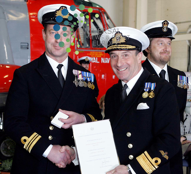 Lieutenant Commander Martin Ford receiving their awards for operational bravery from Rear Admiral Simon Charlier