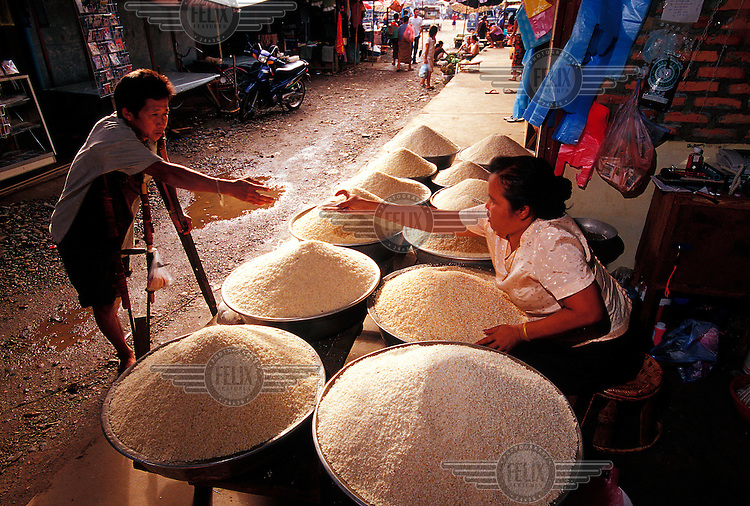 Amputee at the market stall of a rice trader. Laos has the second highest per capita rice consumption in the world, with the average Laotian consuming 170kg of rice a year.