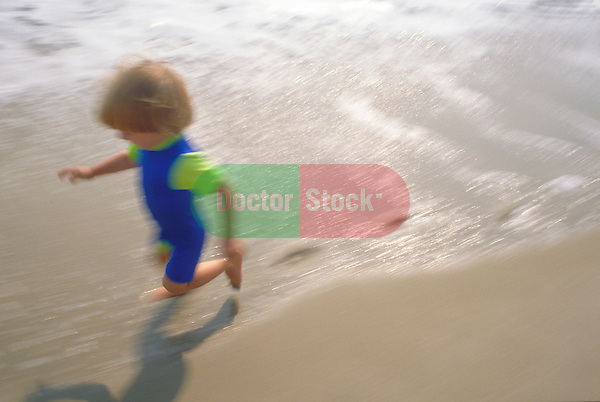 young boy running at beach