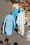 Three women wearing white and blue robes, walk through the Souk in Marrakesh, Morocco.