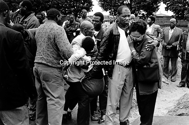 SOWETO, SOUTH AFRICA MAY 3: An unidentified relative faints during a funeral at Roodeport Cemetary for Jessica Ngcongwane, age 28, who died a few days earlier in an Aids related disease on May 3, 2003 in Soweto, South Africa. She was buried along with four other people on the same time. South Africa has seen a big increase in funerals since the HIV-Aids epidemic has grown and Jessica is one of many young people who are dying of HIV/Aids. Her family decided to come out in public about her disease to help other people get rid of the stigma about Aids in their communities. HIV-Aids affects many people in South Africa, but many still have problems to talk about it. South Africa has one of the highest aids infection rates in the world and its estimated that about six hundred people die each day..Photo: Per-Anders Pettersson/iAfrika Photos....