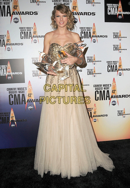 TAYLOR SWIFT.Attending the 43rd Annual CMA Awards held at the Sommet Center, Nashville, Tennessee, USA, 11th November 2008..pressroom press room country music .full length gold strapless sequin sequined beige tulle long maxi gown dress winner trophies .CAP/ADM/GS.©George Shepherd/AdMedia/Capital Pictures.