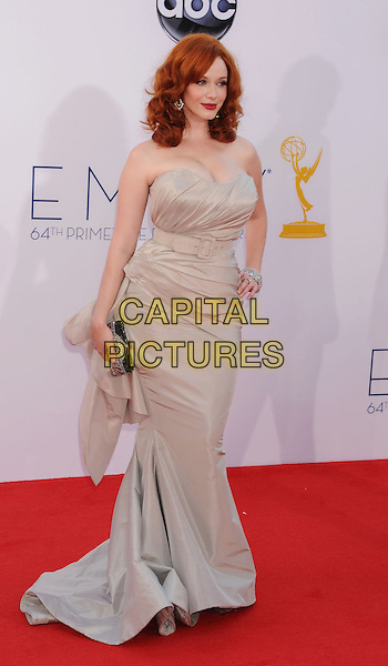 Christina Hendricks .The 64th Anual Primetime Emmy Awards held at Nokia Theatre L.A. Live in Los Angeles, California, USA..September 23rd, 2012.emmys full length silver beige strapless dress cleavage hand on hip clutch bag  .CAP/ROT/TM.© TM/Roth/Capital Pictures