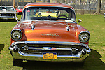 Floral Park, New York, U.S. - April 27, 2014 - An orange 1957 Chevrolet Bel Air, with chrome front grille and hood ornaments, is exhibited by members of the New York Antique Auto Club at the 35th Annual Antique Auto Show at Queens Farm.