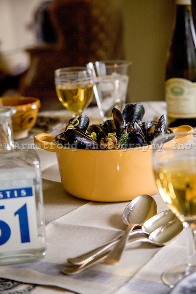 Pot of mussels on a table with glasses of white wine and pastis.