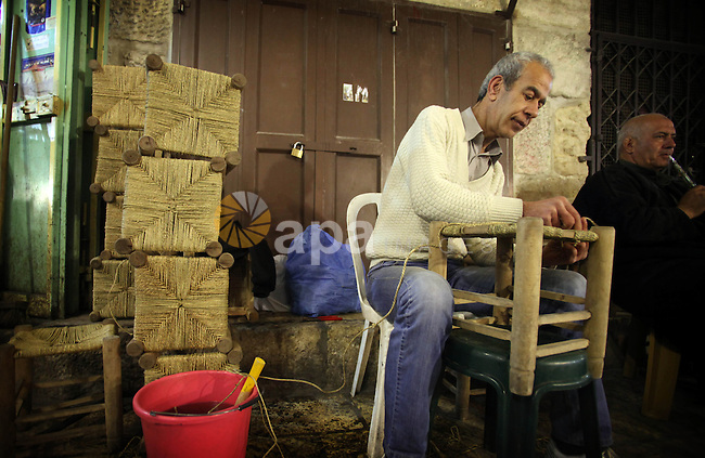 A Palestinian man works on traditional chairs made from straw in front of his workshop in Jerusalem's Old City on February 12, 2014. Minister of Holy Places for the PA Mahmoud al-Habbash told Israel's Channel 10 network that the PA wants control of all the areas in Jerusalem that were won by Israel during the 1967 Six-Day War, including the Western Wall. Photo by Saeed Qaq