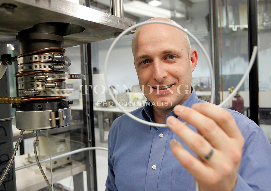 Aaron Crumm, President and Founder of Adaptive Materials, Inc., holds up a spool of miniature extruded fuel cell, made by the machine on his left, at his company's research and development lab on Monday, April 10, 2006 in Ann Arbor, Mich. These ceramic and plastic tubes, key components of AMI's fuel cell technology, are hardened in a kiln and stacked to form fuel cells.