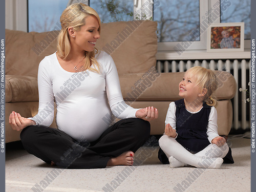 Happy pregnant mother and her little daughter having fun together doing yoga at home