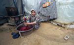 Fadia, who escaped fighting in Aleppo, Syria, washes clothes in front of her family's shelter in the Aamer al Sanad refugee settlement in Kab Elias, a town in Lebanon's Bekaa Valley which has filled with Syrian refugees. Two of her ten children were killed in Syria's civil war. <br /> <br /> Lebanon hosts some 1.5 million refugees from Syria, yet allows no large camps to be established. So refugees have moved into poor neighborhoods or established small informal settlements in border areas. International Orthodox Christian Charities, a member of the ACT Alliance, provides support for refugees in Kab Elias, including a community clinic.