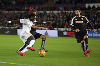 Bafetimbi Gomis of Swansea (L) takes on two Watford players before his shot at goal went wide during the Barclays Premier League match between Swansea City and Watford at the Liberty Stadium, Swansea on January 18 2016