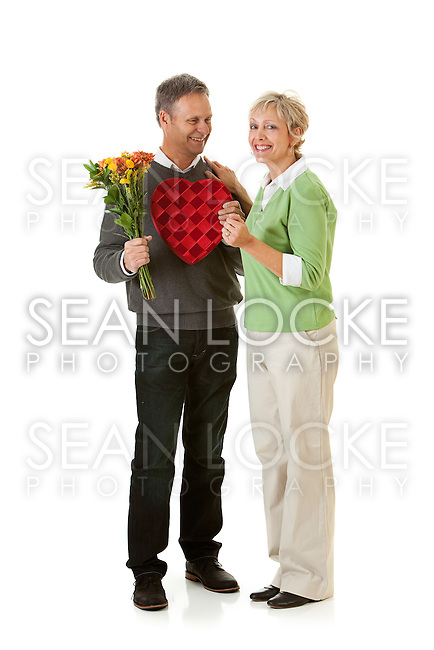 Series with a mature couple, mid 50's, in various themes, including healthy eating, medical and fun.  Isolated on white and an interior room.  Holding heart shaped candy box for Valentine's Day