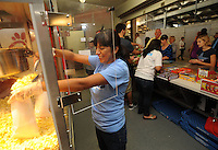 NWA Democrat-Gazette/ANDY SHUPE<br /> Maritza Pratt, a parent of a volleyball student-athlete at Har-Ber High School in Springdale and a member of the team's booster club, serves popcorn Friday, Sept. 25, 2015, while working in a concession stand at Wildcat Stadium.