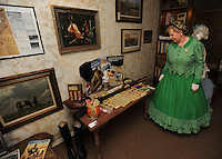 NWA Democrat-Gazette/ANDY SHUPE<br /> Anita Burney, director of the Elm Springs Historical Society, leads a tour Saturday, Aug. 22, 2015, past a Springfield rifle during an open house at the society's Heritage Center in Elm Springs. The group plans to further develop the center's offerings and to host activities in the future to celebrate the historical significance of the town.