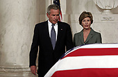 United States President George W. Bush (L) and First Lady Laura Bush pause next to Chief Justice William Rehnquist's flag-draped casket Sept. 6, 2005 in the Great Hall of the Supreme Court in Washington, DC. Rehnquist's casket will lie in repose at the court until the next morning and he will be buried in a private ceremony at Arlington Cemetery that afternoon. <br /> Credit: Chip Somodevilla / Pool via CNP