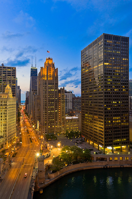 """Dusk view of Michigan Ave. also known as The Magnificent Mile with The Wrigley Building to the left and The Chicago Tribune Tower to the right. The Hancock Building is in the background with its twin antennas. The architecture of Chicago has influenced and reflected the history of American architecture. The city of Chicago, Illinois features prominent buildings in a variety of styles by many important architects. Since most buildings within the downtown area were destroyed by the Great Chicago Fire in 1871, Chicago buildings are noted for their originality rather than their antiquity..Beginning in the early 1880s, architectural pioneers of the Chicago School explored steel-frame construction and, in the 1890s, the use of large areas of plate glass. These were among the first modern skyscrapers and amongst their most famous architects were William LeBaron, John Wellborn Root Sr., Daniel Burnham and Charles Atwood. Louis Sullivan was perhaps the city's most philosophical architect. Realizing that the skyscraper represented a new form of architecture, he discarded historical precedent and designed buildings that emphasized their vertical nature. This new form of architecture, by Jenney, Burnham, Sullivan, and others, became known as the """"Commercial Style,"""" but it was called the """"Chicago School"""" by later historians..Since 1963, a """"Second Chicago School"""" emerged, largely due to the ideas of structural engineer Fazlur Khan. Some of Chicago's skyscrapers such as the John Hancock Center, Willis Tower (formerly known as the Sears Tower) and The Trump International Hotel and Tower are amongst the tallest buildings in the world."""